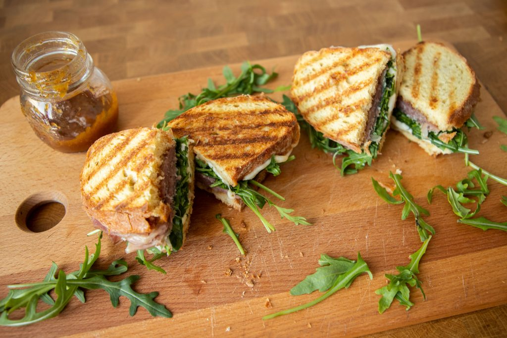 These prosciutto and mozzarella panini have a secret ingredient that ramp them up a notch to be the best sandwich you've ever tried!