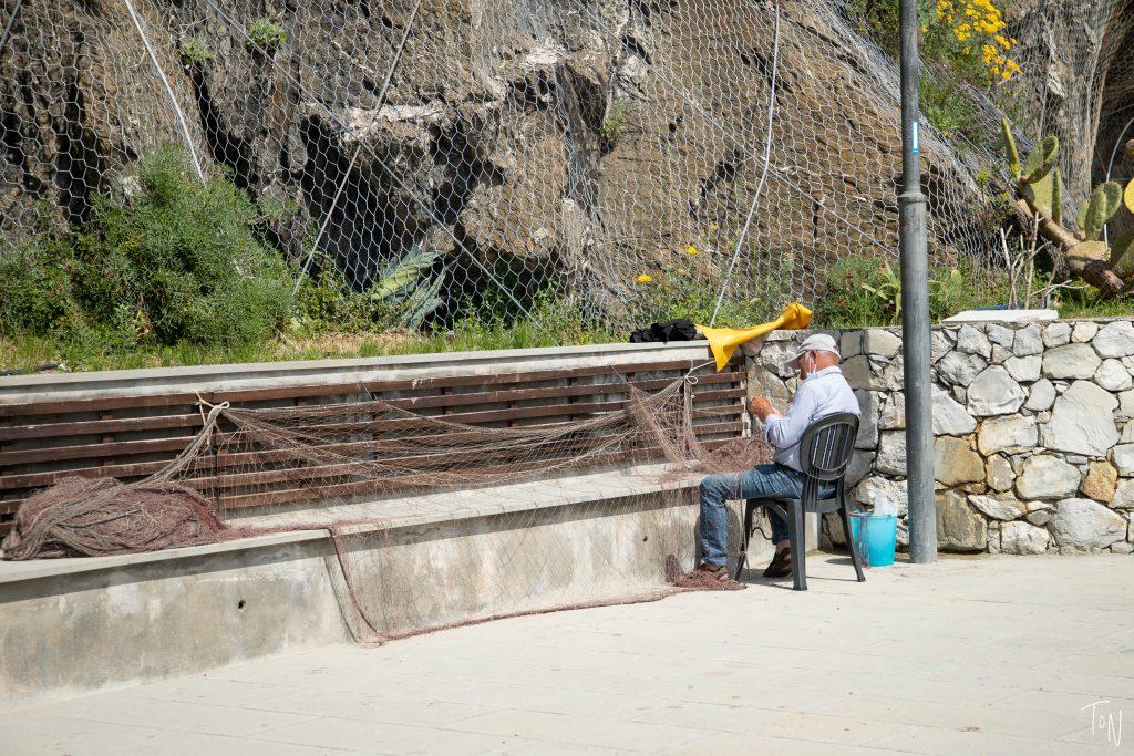 fisherman mending nets cinque terre